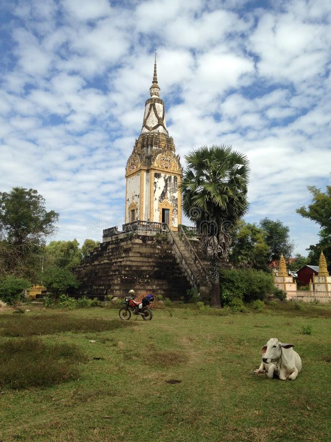 Ancient cambodian temple. Cow next to the building, lonely motorbike, no people. Abandoned place, rural area. Travel destination - Kampong Thom, North of royalty free stock photo