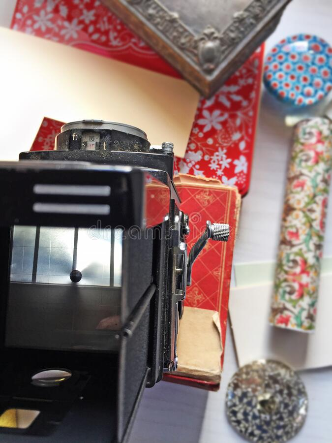 Ancient camera on a desk. View from above. Film camera resting on old book and boxes stock photo