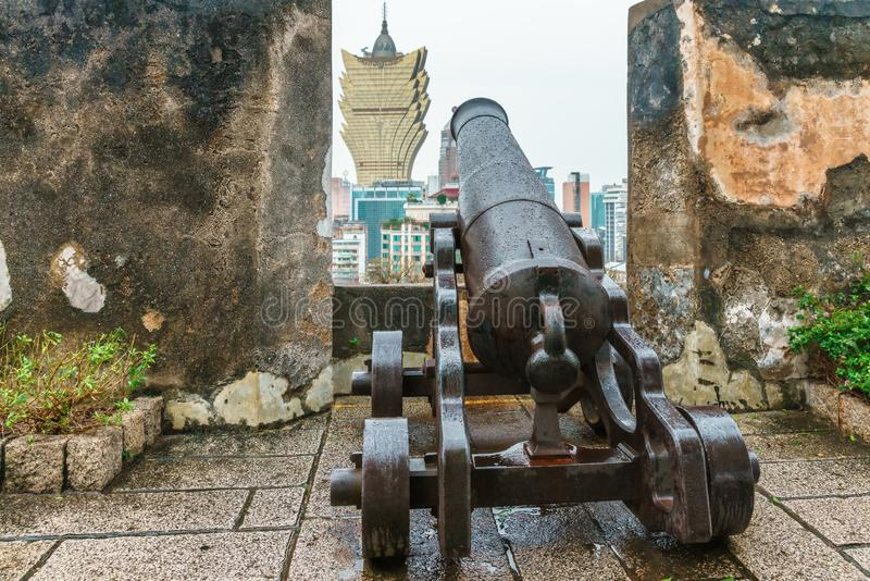 Ancient cannon on top platform of The Mount Fortress Museum of History aimed on skyscraper of The Grand Lisboa Hotel stock photo