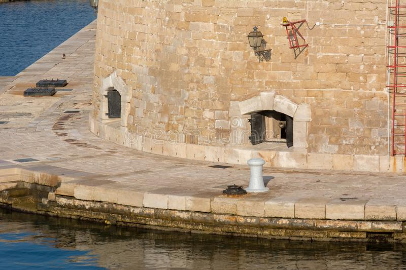 Ancient Cannon in the Wall of the Castello Aragonese alongside t. He Taranto Canal Boat in a Sunny Day stock image
