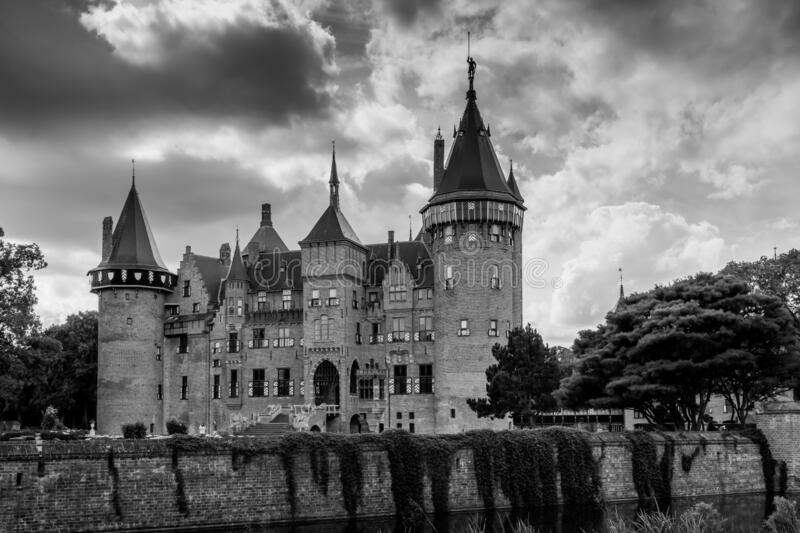 Castle in dramatic sky. Ancient castle surrounded by walls in dramatic sky, picture in black and white. Castle with many towers and gates stock photos