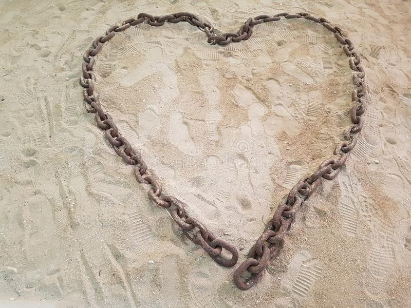 Ancient chain placed on the sand and depicting a solid love. stock photos