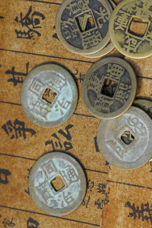 Ancient Chinese coins on a text back. Ancient Chinese coins on a Chinese calligraphy or text background royalty free stock photo