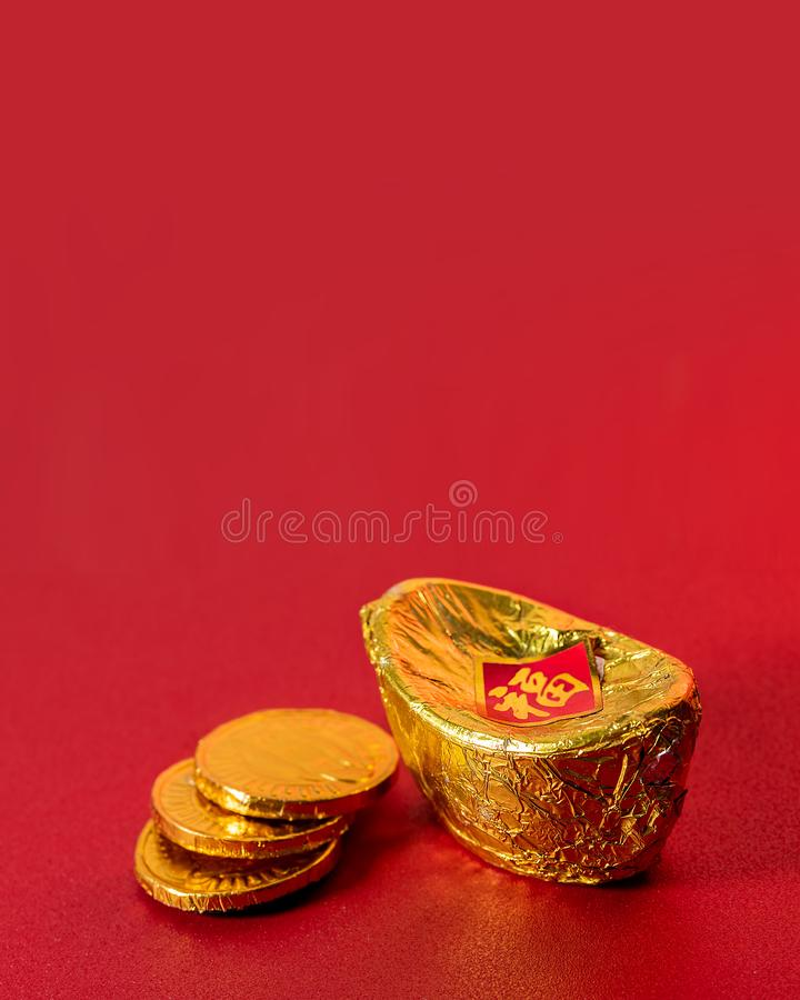 Ancient Chinese Gold Ingot with Three Golden Coins Made From Alumunium Foil on Red Background For Chinese Lunar New Year Greeting royalty free stock images