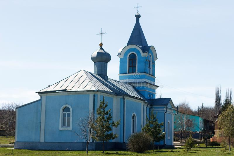 Ancient church of blue color in village. In springtime stock photos