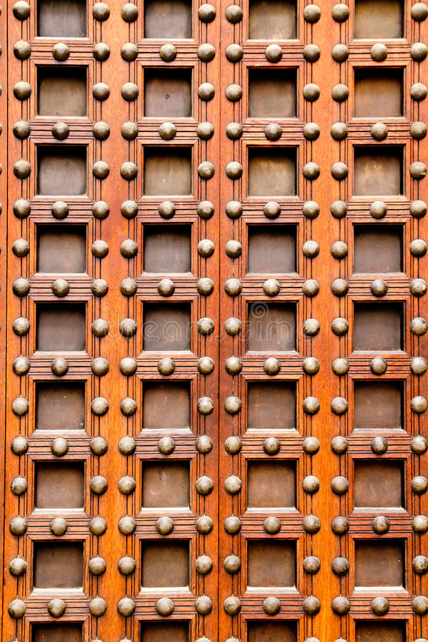 Ancient church castle wooden door with nails. And little square shapes in spain royalty free stock photos