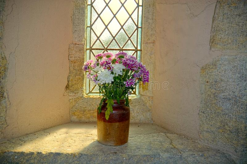 Ancient church interior. Pot of flowers. A pot of flowers on a window ledge in an ancient church as the light floods in from the leaded window stock images