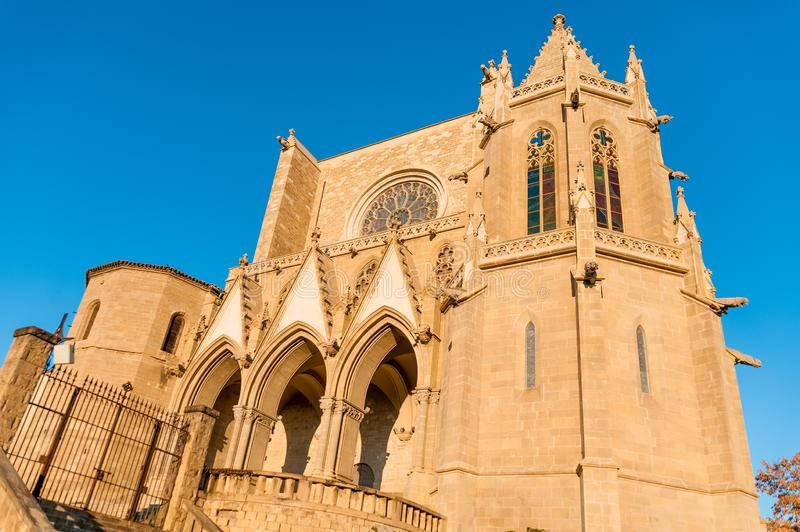 View of Collegiate Basilica of Santa Maria Seu in Manresa city in catalunya region in Spain, with trees and clear blue sky during. Ancient church at sunset in royalty free stock photography