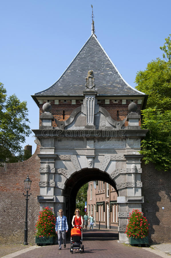 Ancient city gate Veerpoort and walking family. Netherlands, South Holland province; region, area Krimpenerwaard; city; small town Schoonhoven: In the street Wal royalty free stock photography