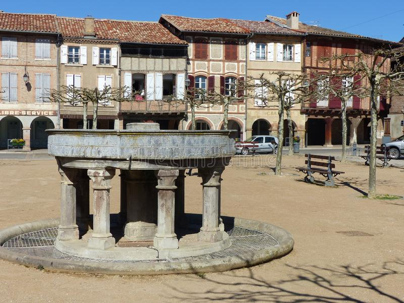 Ancient classified fountain of Lisle of Tarn in south of France. Blue clear sky. Sunny day. Springtime  and holidaytime. Characteristic colored ancient houses royalty free stock images