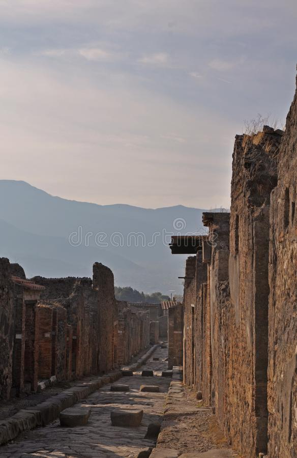 An ancient cobbled street in the ruins of Pompeii, Italy. Roman town destroyed by Vesuvius volcano. royalty free stock photos