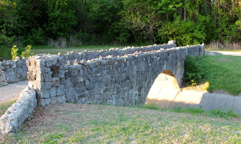 Medieval Foot Bridge. Ancient Cobblestone medieval foot bridge traveling across a drainage ditch stock photos