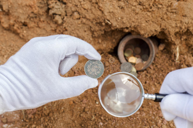 Ancient coins and magnifier. royalty free stock photography