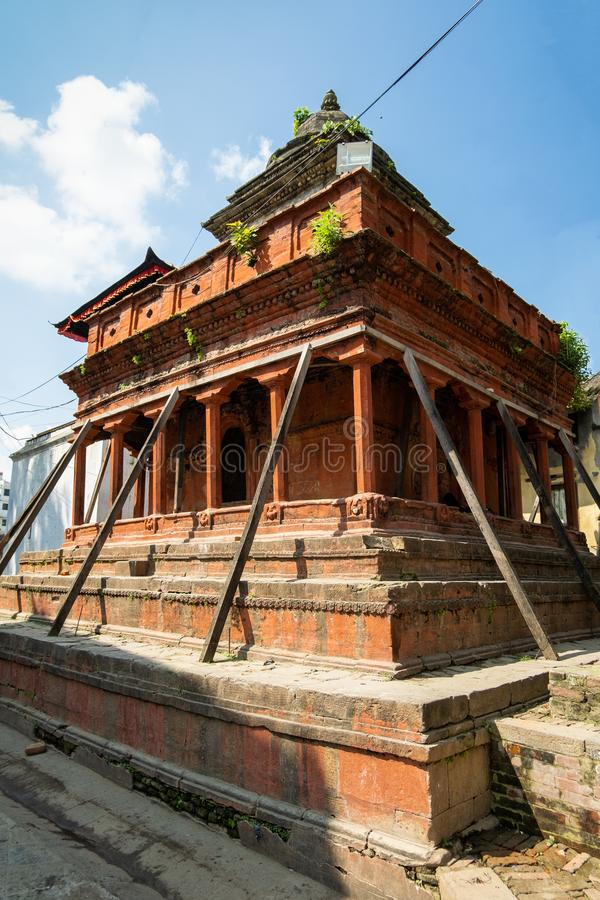 An ancient collapsing Hindu temple on a stone pedestal with wooden pillars. Durbar Square in Kathmandu, Nepal. An ancient collapsing Hindu three-story temple on royalty free stock image