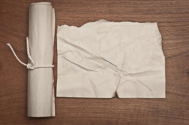 Ancient crumpled paper scroll on wood table may use for background royalty free stock image