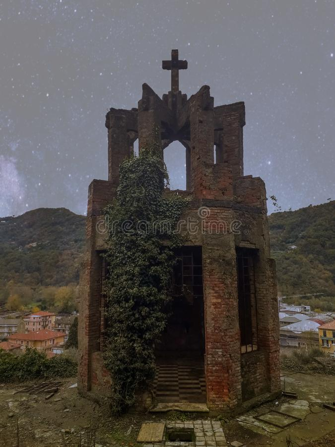 Ancient crypt. In red stone invaded by vegetation surrounded by a mountain landscape and homes in Genoa, Italy royalty free stock images