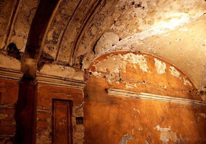 Ancient dark arched ceiling with peeling plaster. Ancient dark arched ceiling in evening light stock image