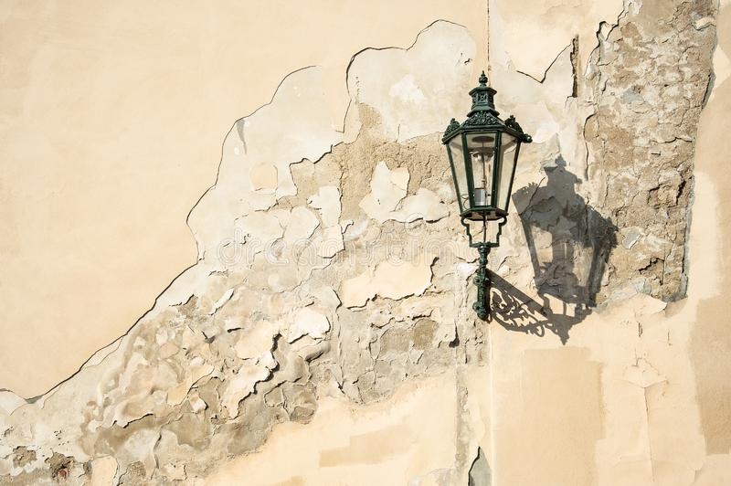An ancient dark green squiggly lantern casting a cloud over a grungy house wall in Prag royalty free stock photography