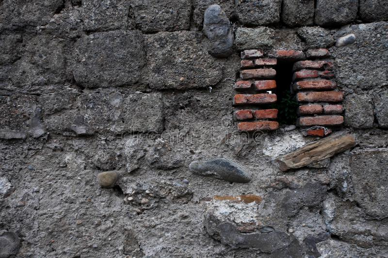 Ancient dark wall of gray stones, red loopholes of red brick, ch. Aotic masonry. background royalty free stock image
