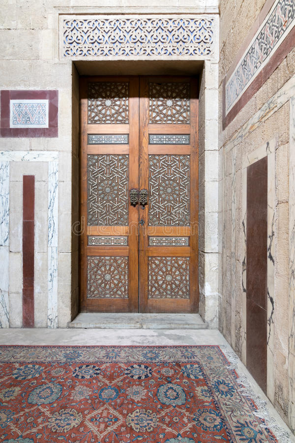 Ancient decorated door arabesque and decorated colored marble wall royalty free stock photography