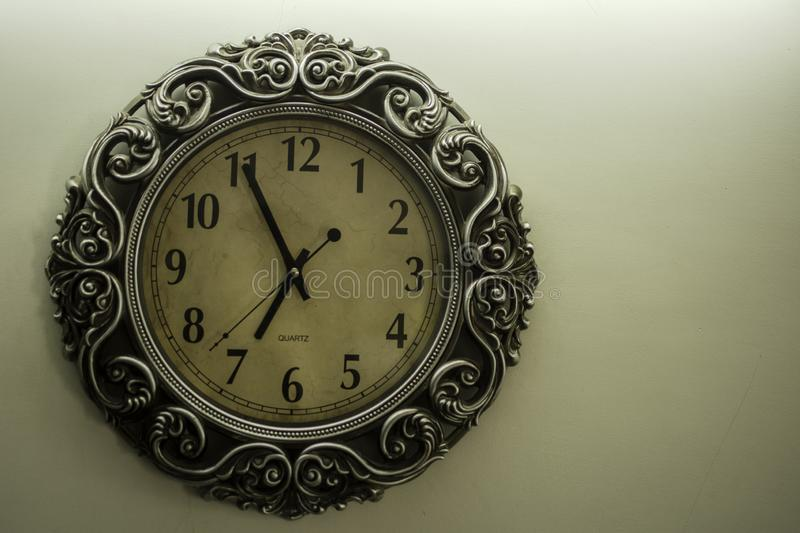 Ancient Designer Wall Clock With Light Yellow Back Ground showing time 06.55 o`clock and free spac on right side stock photo