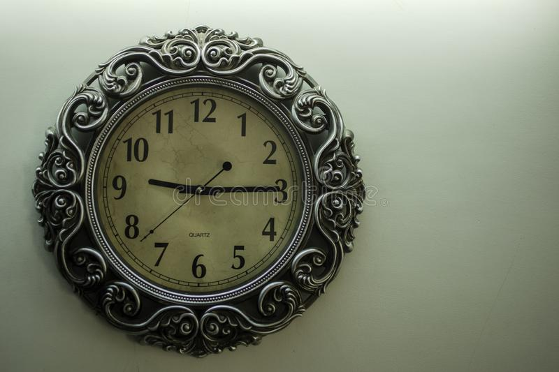 Ancient Designer Wall Clock With Light Yellow Back Ground showing time 09:15 o`clock and free spac on right side stock photo