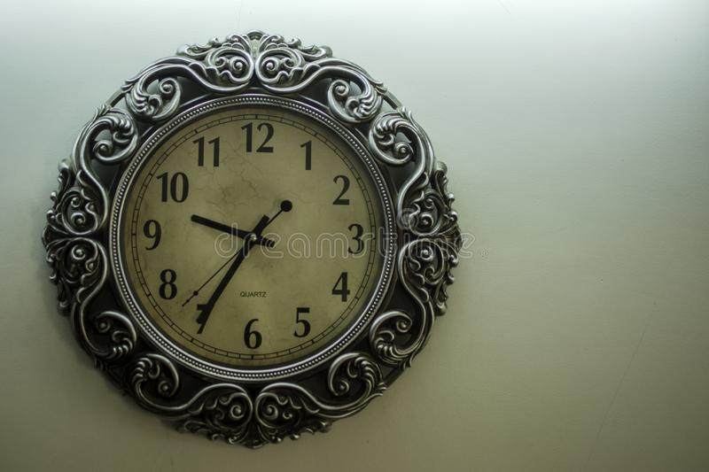 Ancient Designer Wall Clock With Light Yellow Back Ground showing time 09:35 o`clock and free spac on right side stock photo