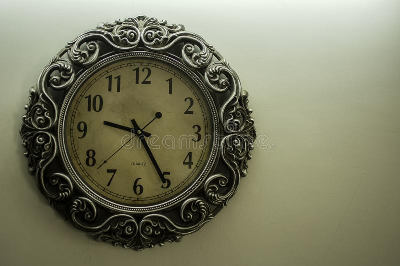 Ancient Designer Wall Clock With Light Yellow Back Ground showing time 09:25 o`clock and free spac on right side stock photo