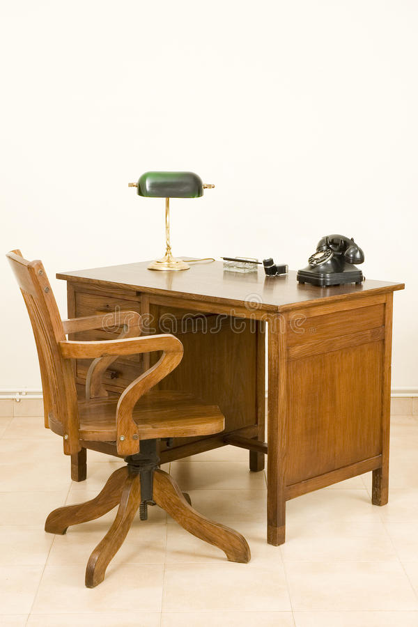 Ancient desk. And chair with lamp and telephone stock images