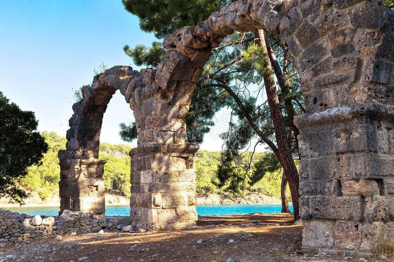 Ancient destroyed aqueduct of the city of Phaselis, Turkey, Kemer in sunny summer day. Sea on background royalty free stock image