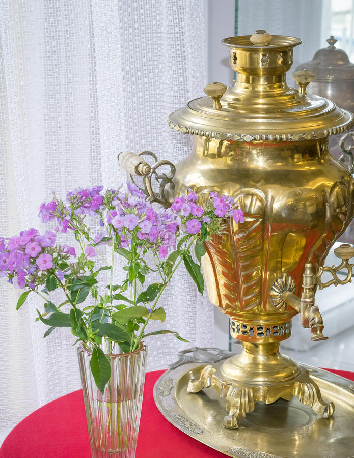 Ancient device for making tea and vase of flowers by the window. The concept of home tea in the family circle stock photos