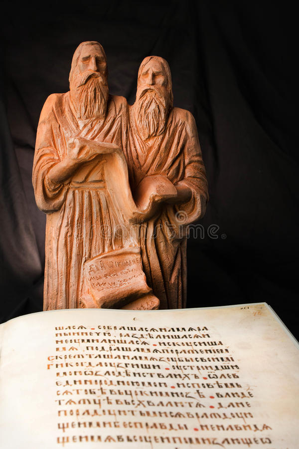 Ancient educators Cyril and Methodius clay statues with antiquarian Bible book with old script. Old christian missionaries for. Slavonic. Yellow pages of old royalty free stock photos