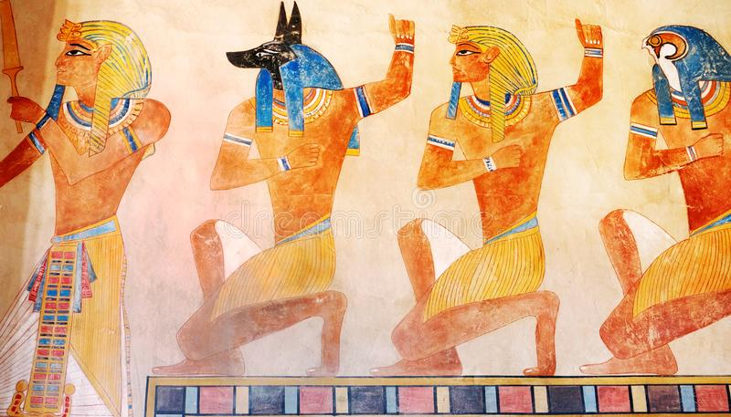 Ancient Egypt scene, mythology. Egyptian gods and pharaohs. Hieroglyphic carvings on the exterior walls of an ancient temple. royalty free stock image