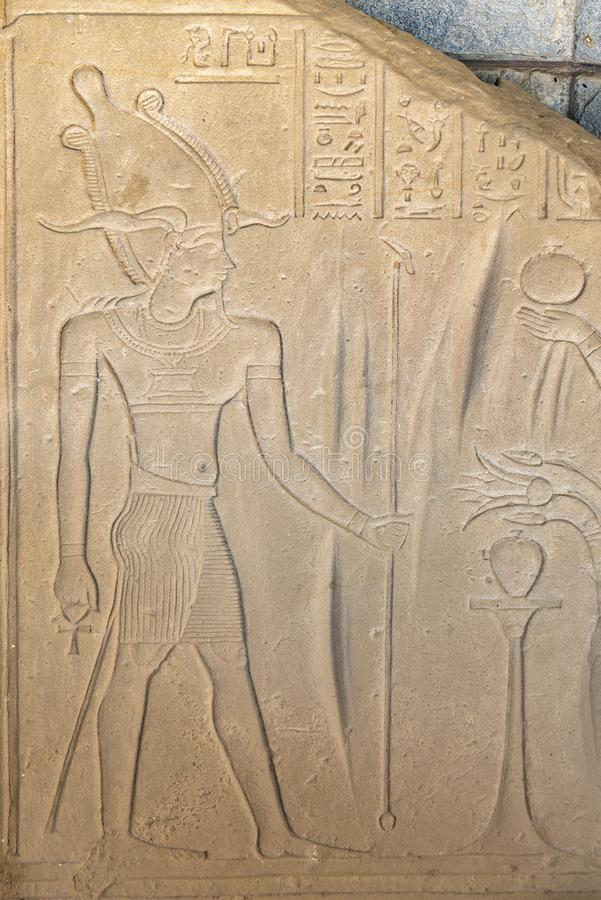 Ancient Egyptian drawings, bas-reliefs with images of people, kings, pharaohs, gods and signs on a stone wall in Aswan stock images