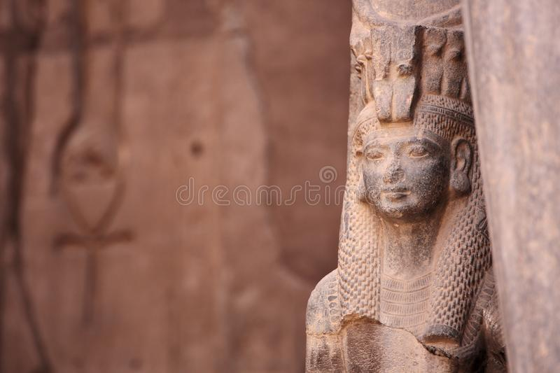 Ancient Egyptian goddess Isis and Ankh the ancient symbol of life. Carved into an ancient temple wall in the background. Karnak, Luxor, Egypt royalty free stock images