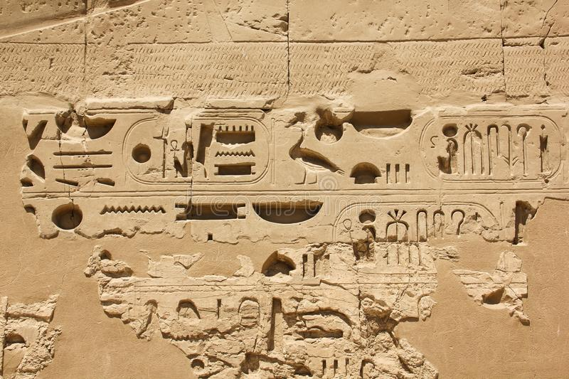 Ancient Egyptian hieroglyphs and symbols carved in stone, preserved fragments in complex of the Karnak temple. Photo taken in egypt clear weather stock photography