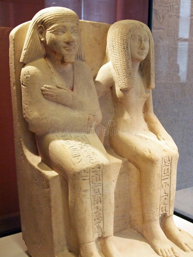 Ancient Egyptian Stone Statues, Seated Male and Female, Louvre Museum, Paris, France royalty free stock images