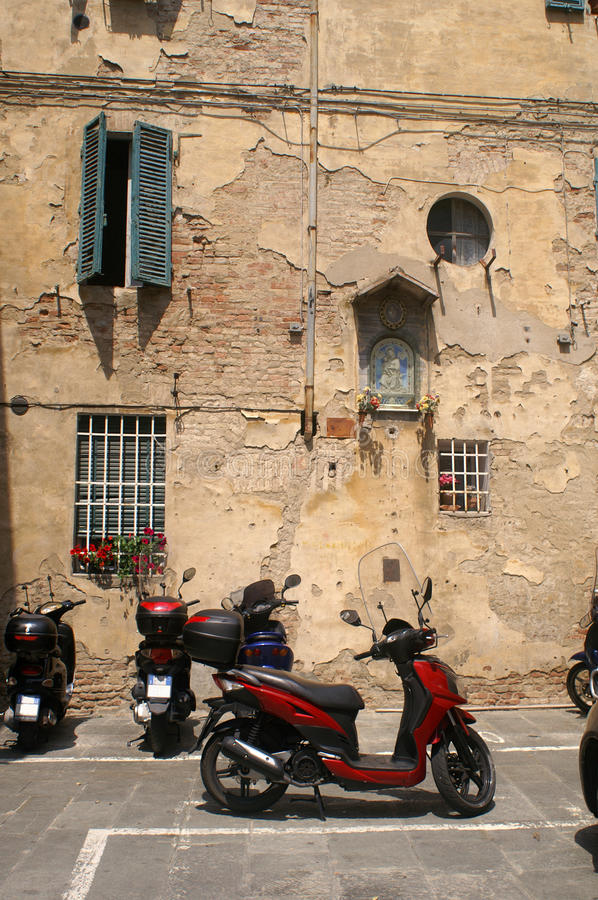 Scooter parked in front of an ancient wall in Sienna Italy