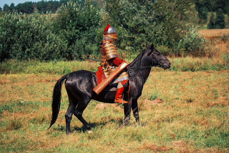 An ancient equestrian in historical costume is reconstructed. The medieval armored knight is on the horse. The historical reenactor is in the summer field stock image