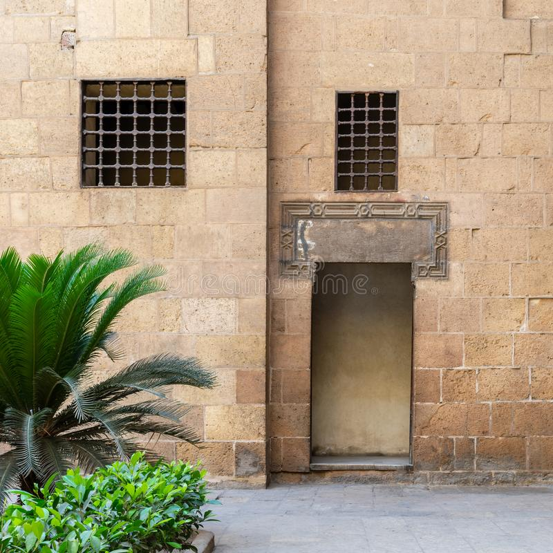 Ancient external old decorated bricks stone wall with two windows and opened door. Leading to Ottoman era Beit El Sehemy historical building, Cairo, Egypt stock photos