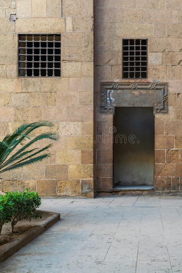 Ancient external old decorated bricks stone wall with windows and opened door. Ancient external old decorated bricks stone wall with two windows and opened door royalty free stock photos