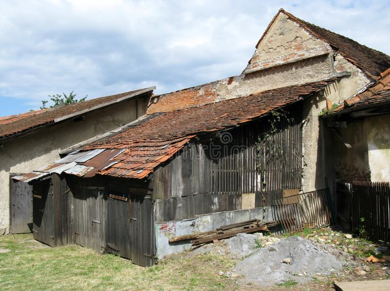 An ancient farmhouse. An old barn with different kinds of roofing stock image