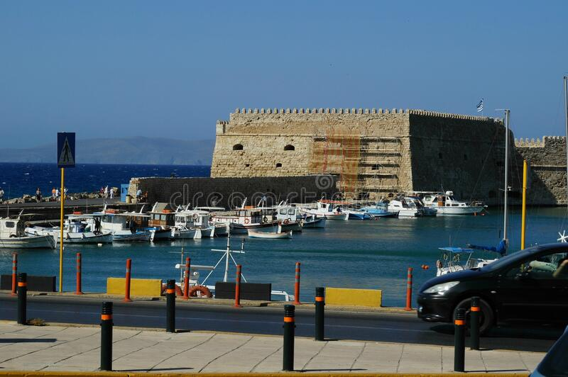 Ancient fortress at the sea port of Agios Nikolaos city, Crete island, Greece at hot summer noon. stock images