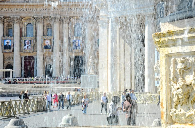 The ancient fountain surrounded by tourists. St. Peter`s Square is located in front of St. Peter`s Basilica in the Vatican City royalty free stock images