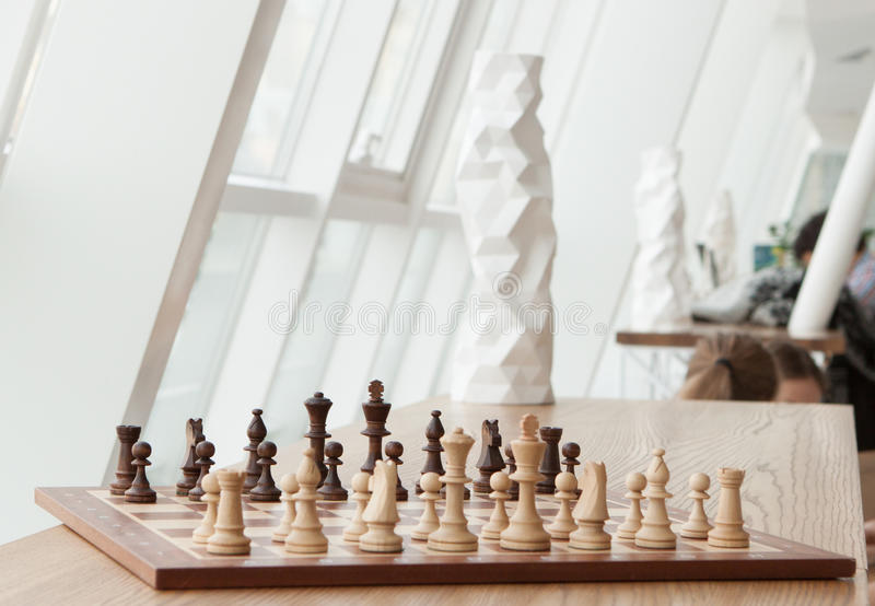 Ancient game in the modern restaurant. Chess standing on a shelf in a modern restaurant royalty free stock image