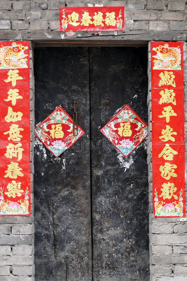 Ancient gate of private residence. In the ancient city, the ancient gate of private residence. The Spring Festival couplet of the winter jasmine is hung on the stock images