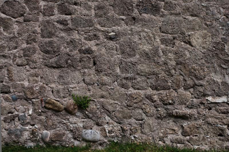 Ancient gloomy wall of gray stones, chaotic laying. Background royalty free stock photo