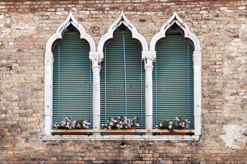 Ancient gothic style window in Venice. Traditional ancient gothic style window with flower pots in Venice, Italy royalty free stock photo
