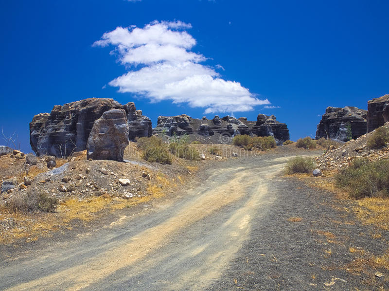 Ancient gravel road through erosion weathering rock formations Plano de El Mojon in the volcanic region of Teguise. Blue sky. Lanzarote, Canary Islands, Spain royalty free stock photo