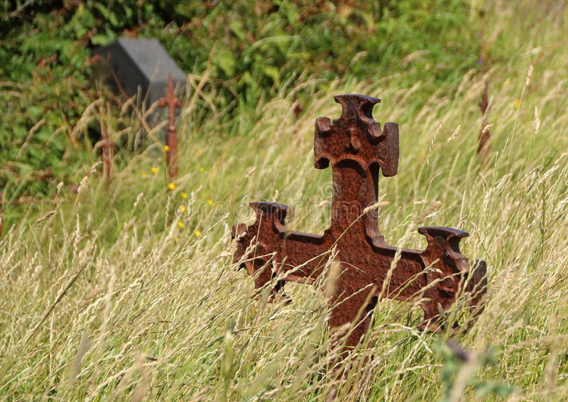 Ancient Graveyard with Rusty Iron Cross in Grass field stock images